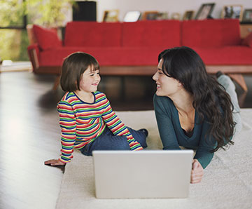 Mother and daughter laying on the ground, using a laptop computer